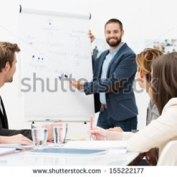 stock-photo-businessman-giving-a-presentation-to-his-colleagues-at-work-standing-in-front-of-a-flipchart-with-155222177
